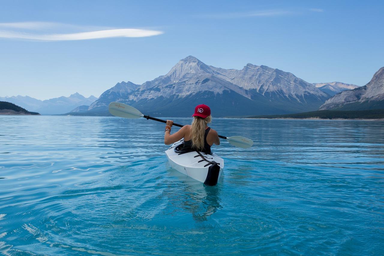 Eine Frau paddelt im boot auf dem See