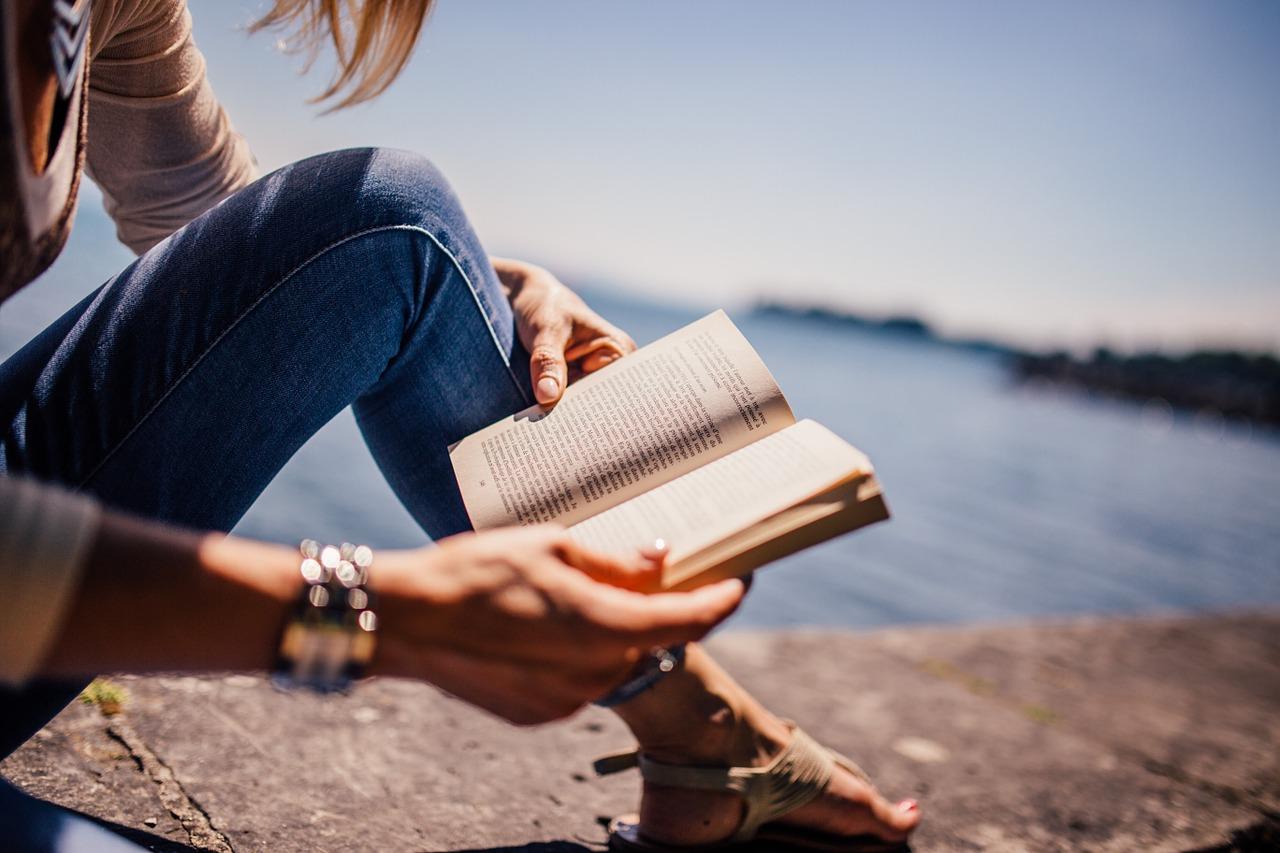 Frau liest ein Buch entspannt am See
