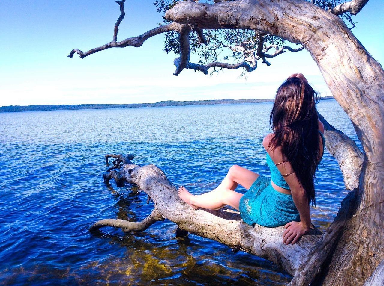 Frau sitzt auf einem Ast oberhalb des Sees
